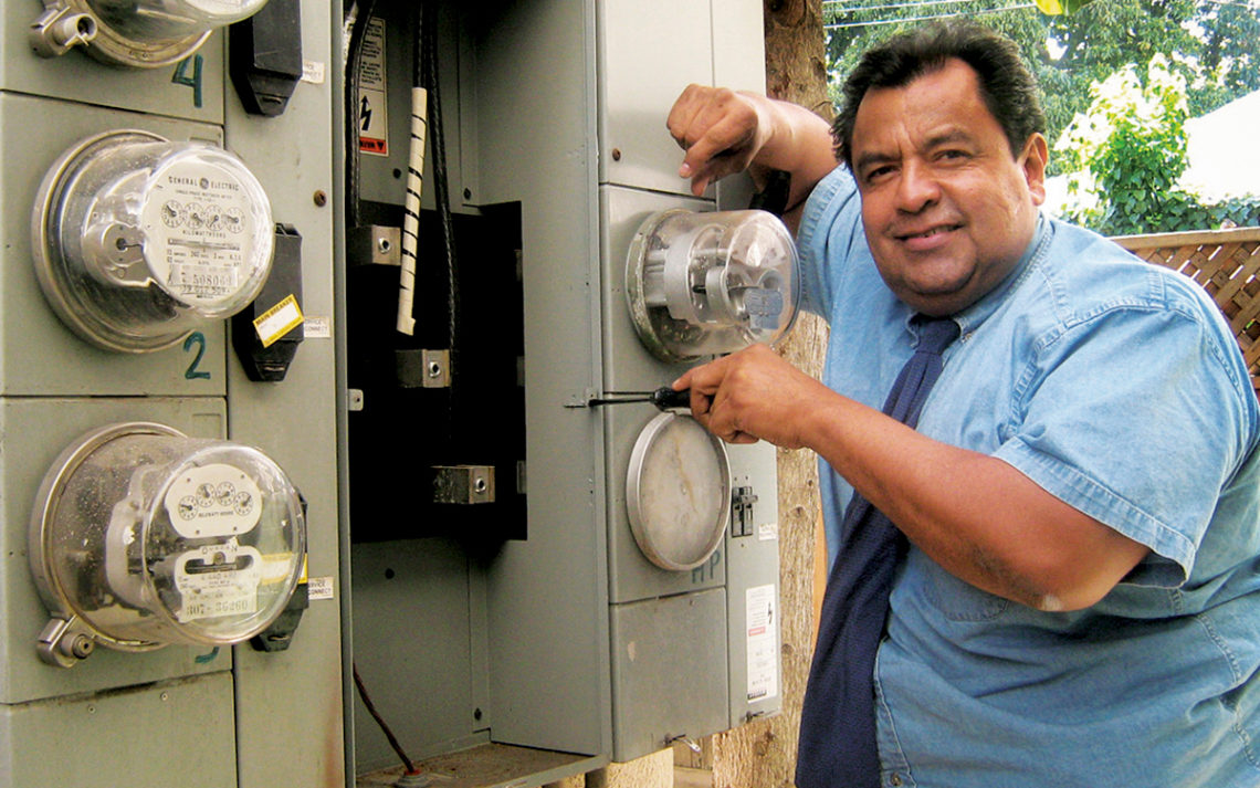 On Demand Electric owner Manuel Berrones works on an electric panel for a customer.