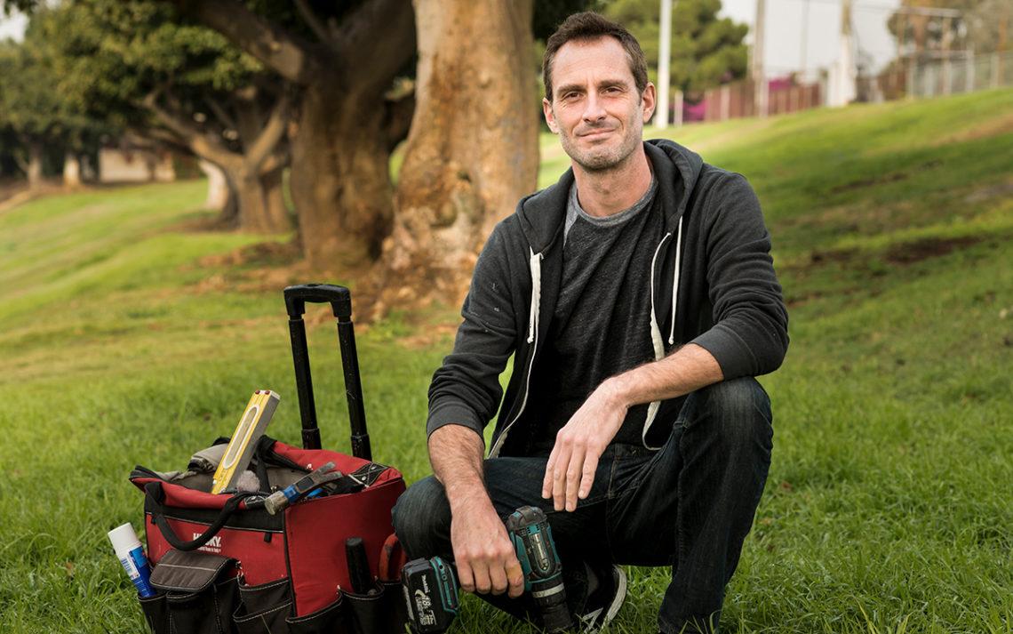 Handyman Ben Brooks kneels by his trusty bag of tools