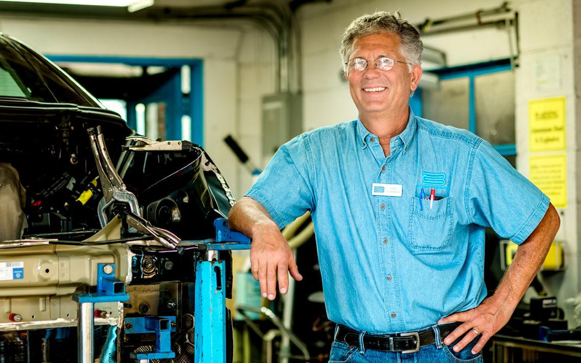 Dan Schimpke, owner of Bevery Coachcraft, oversees a repair in his autobody shop