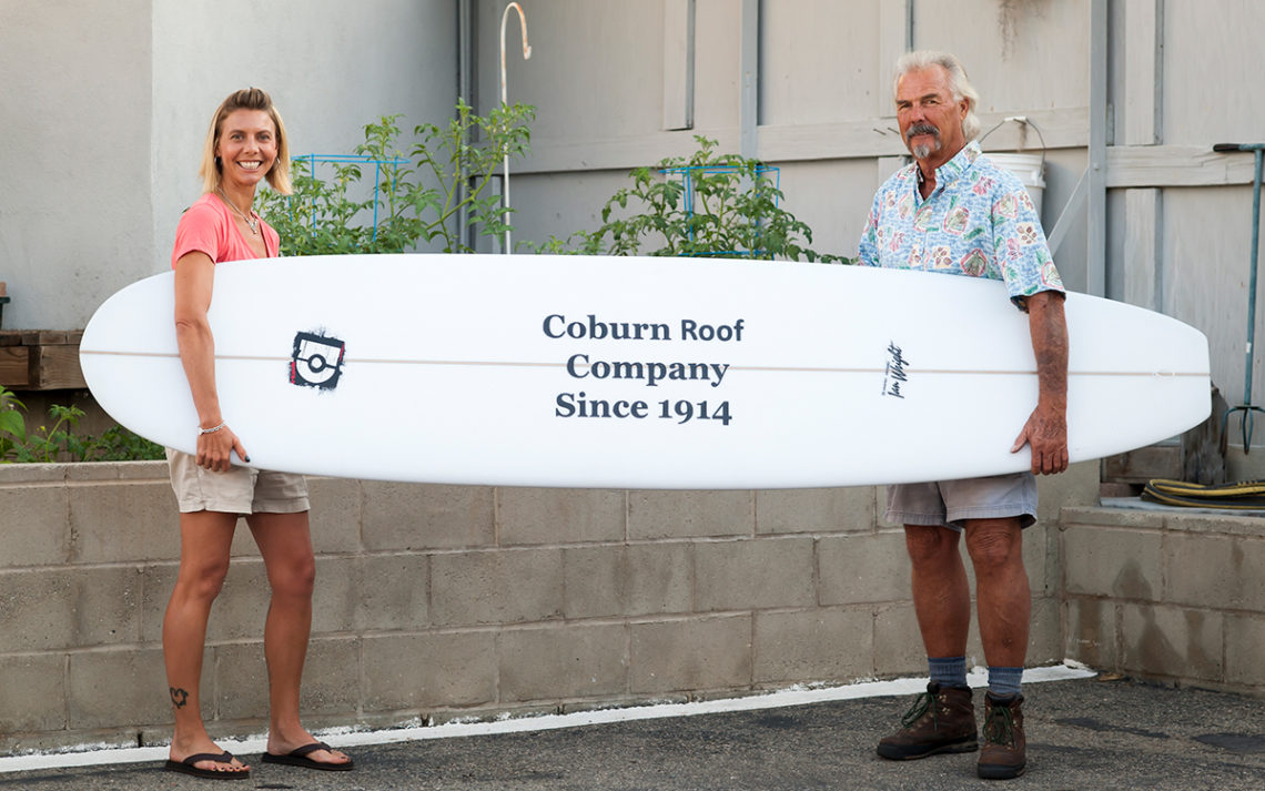 Pat and Kaley Burt of Coburn Roof hold a surf board with the company's name