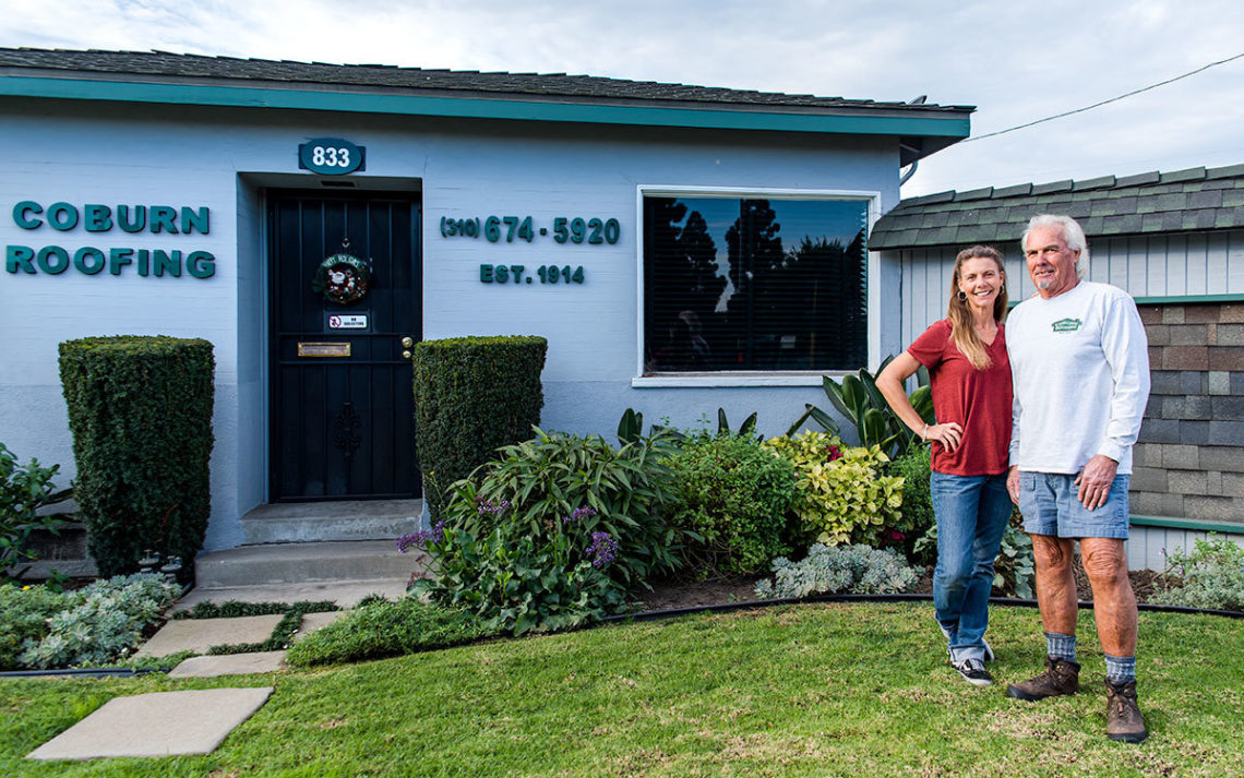 Pat and Kaley Burt of Coburn Roof stand near the Coburn Roofing business house
