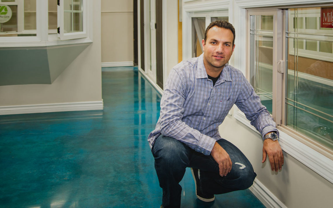 Yoni Barlev of Frontline Windows & More stands in his showroom next to a window.