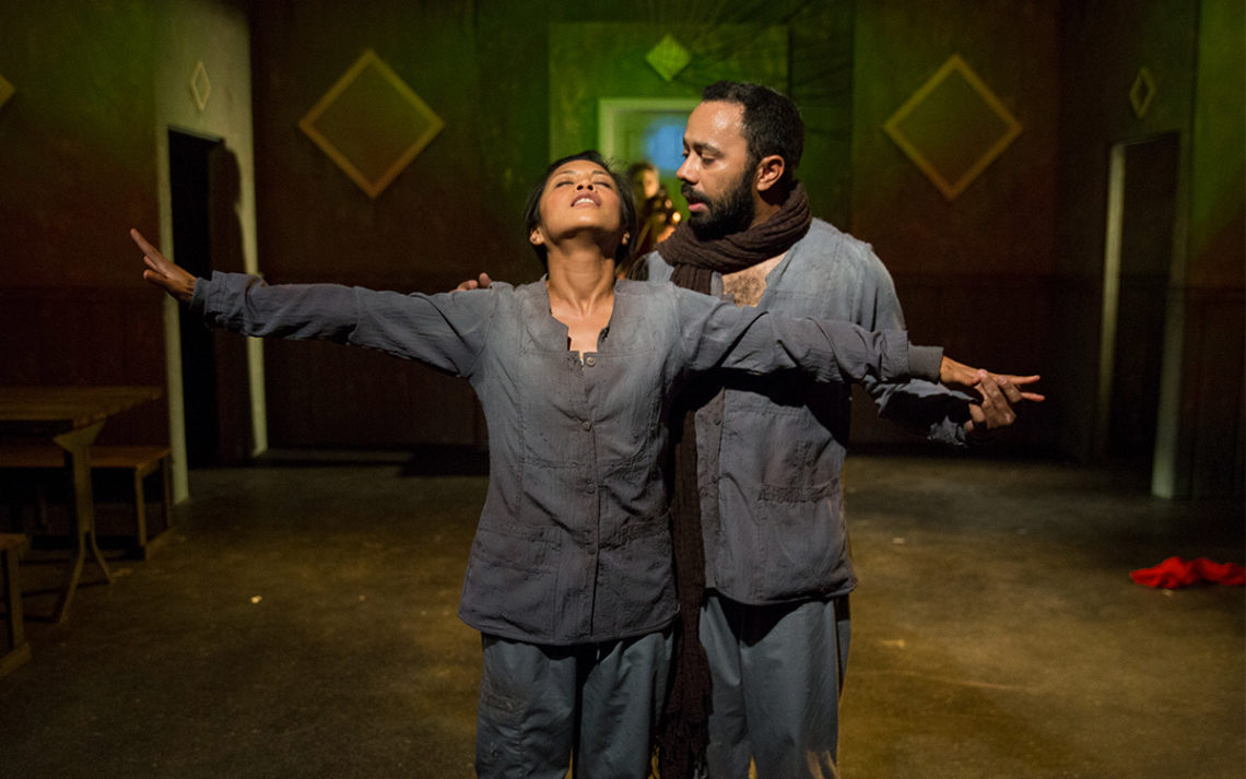 A woman with her arms out and eyes closed and a man talking in the woman's ear on a stage at the Greenway Court Theater.