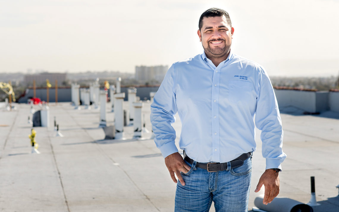 Jobe Carbajal, owner of Jobe Roofing, stands on a commercial building rooftop.