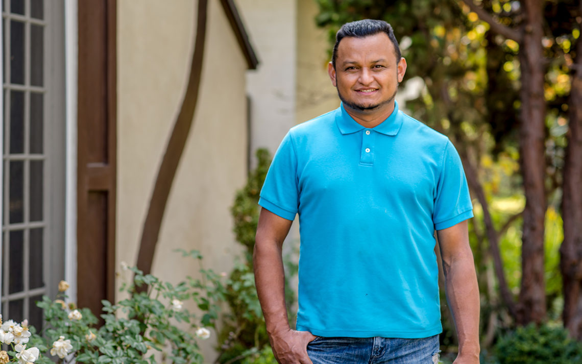 Jose Rivera standing in a backyard.