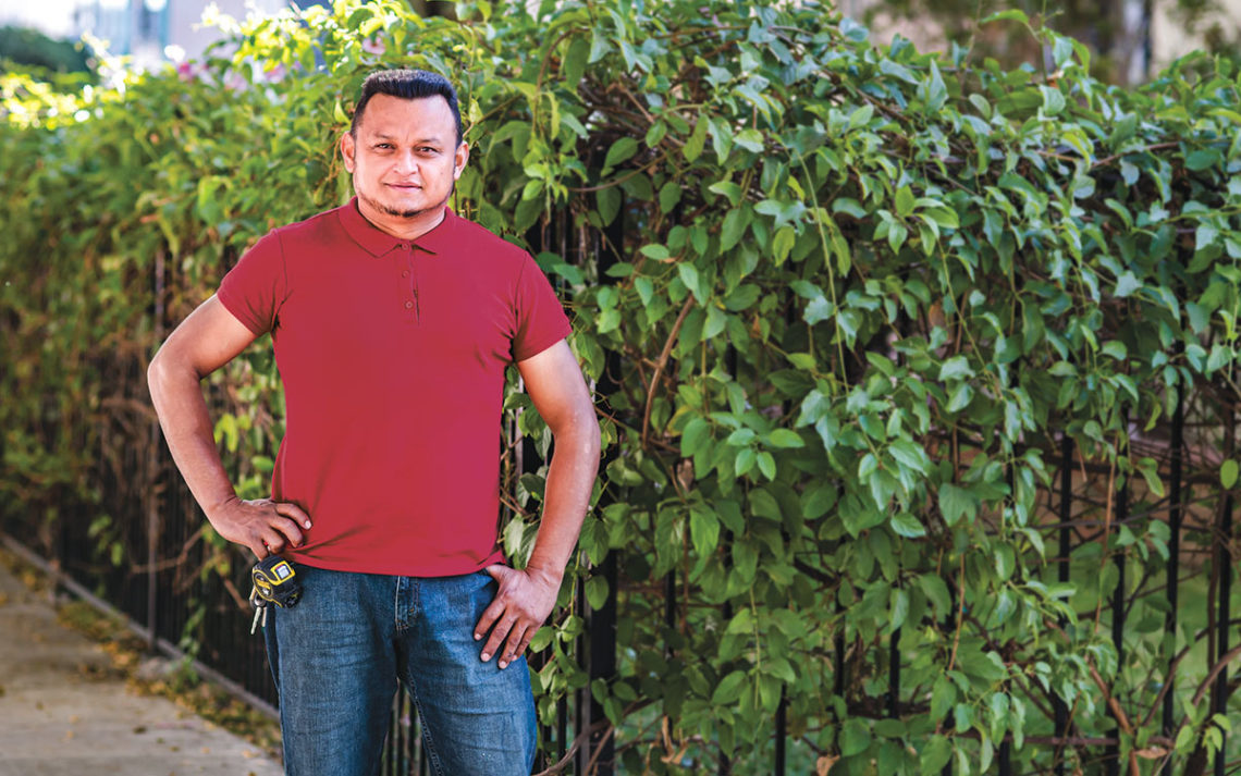 Jose Rivera standing in front of a fence covered in ivy.