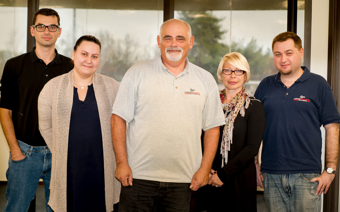 Lerman Appliances Inc. team and family stand together in their office