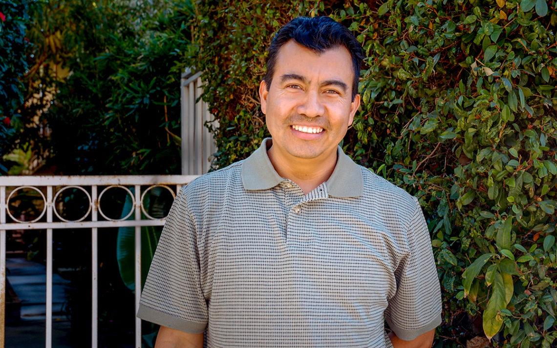 Julio Quintanilla smiles in front of a bush