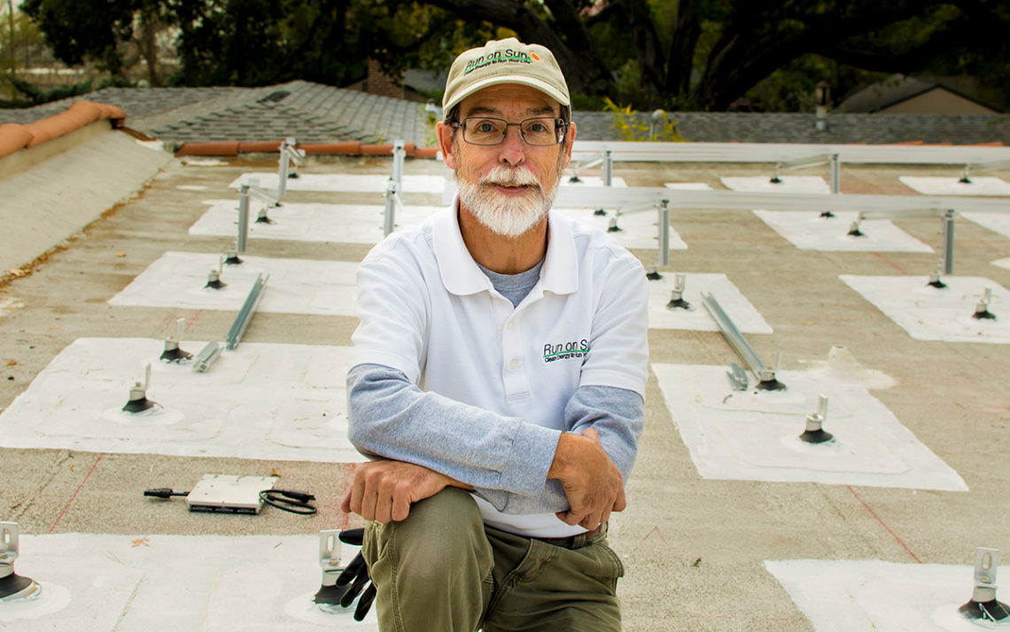 Jim Jenal, owner of Run on Sun, perched on a rooftop with newly installed solar panels.