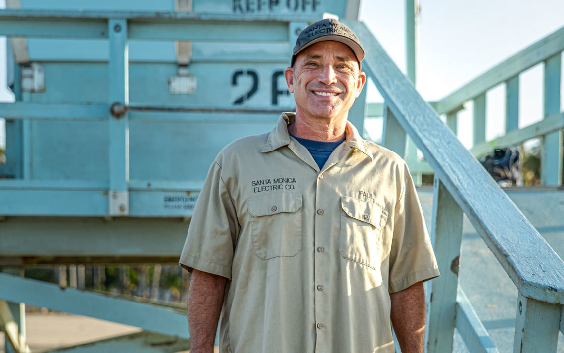 Paul Wegner of Santa Monica Electric smiles in front of the Santa Monica Pier