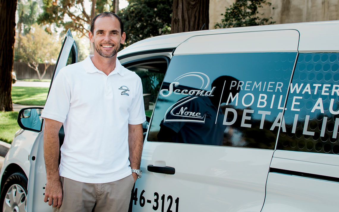 Gabe O'Hara, owner of Second to None Auto Detailing, stands with his work truck