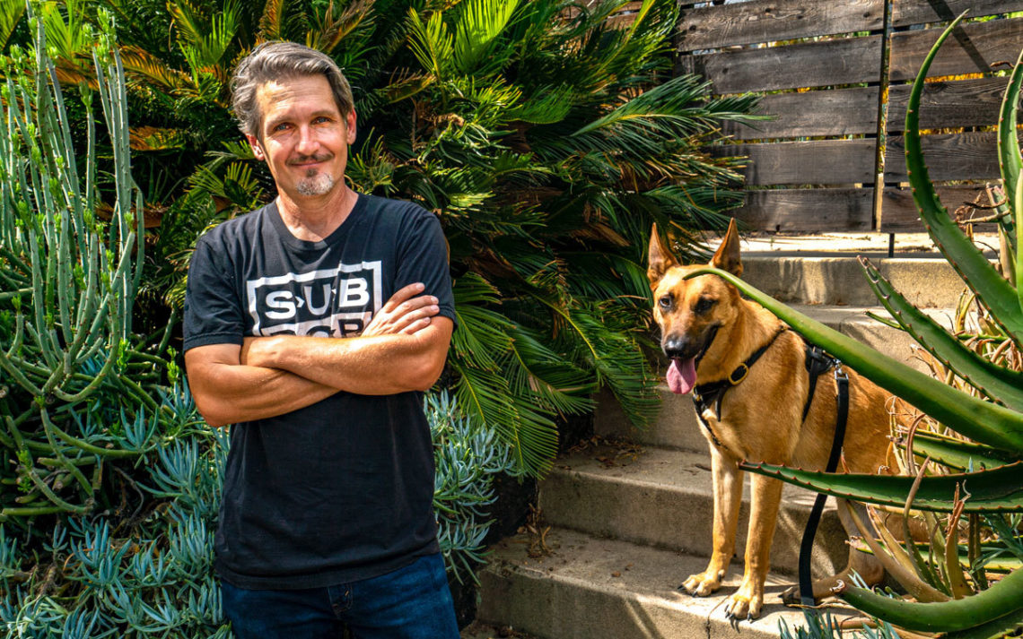 Steve Siegrist with his dog on the front steps of a house