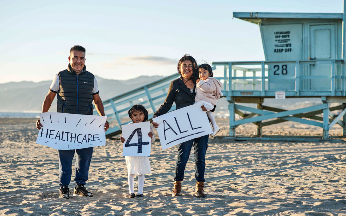 A family standing on the beach, promoting Venice Family Clinic.