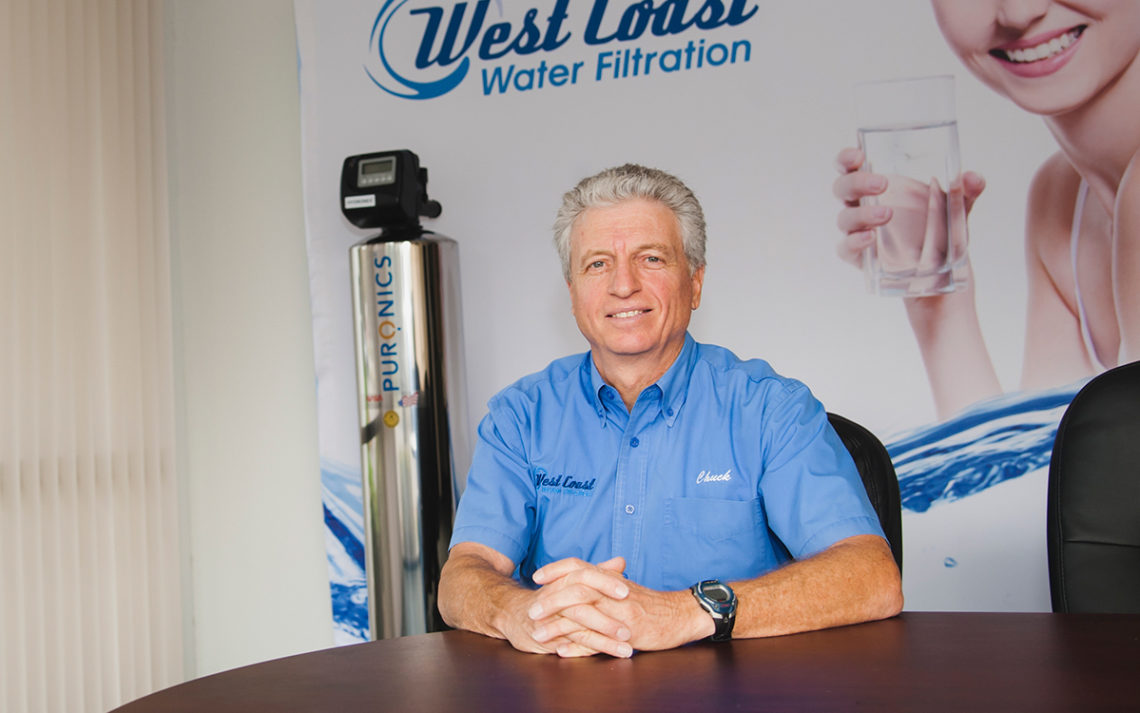 Chuck Wohlberg sits beside a state-of-the-art water filtration system
