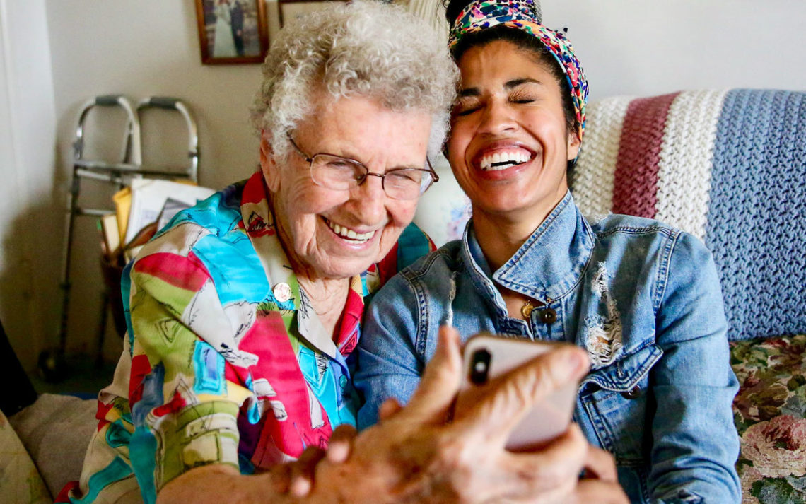 A volunteer from Westside Pacific Villages laughing with an elderly client