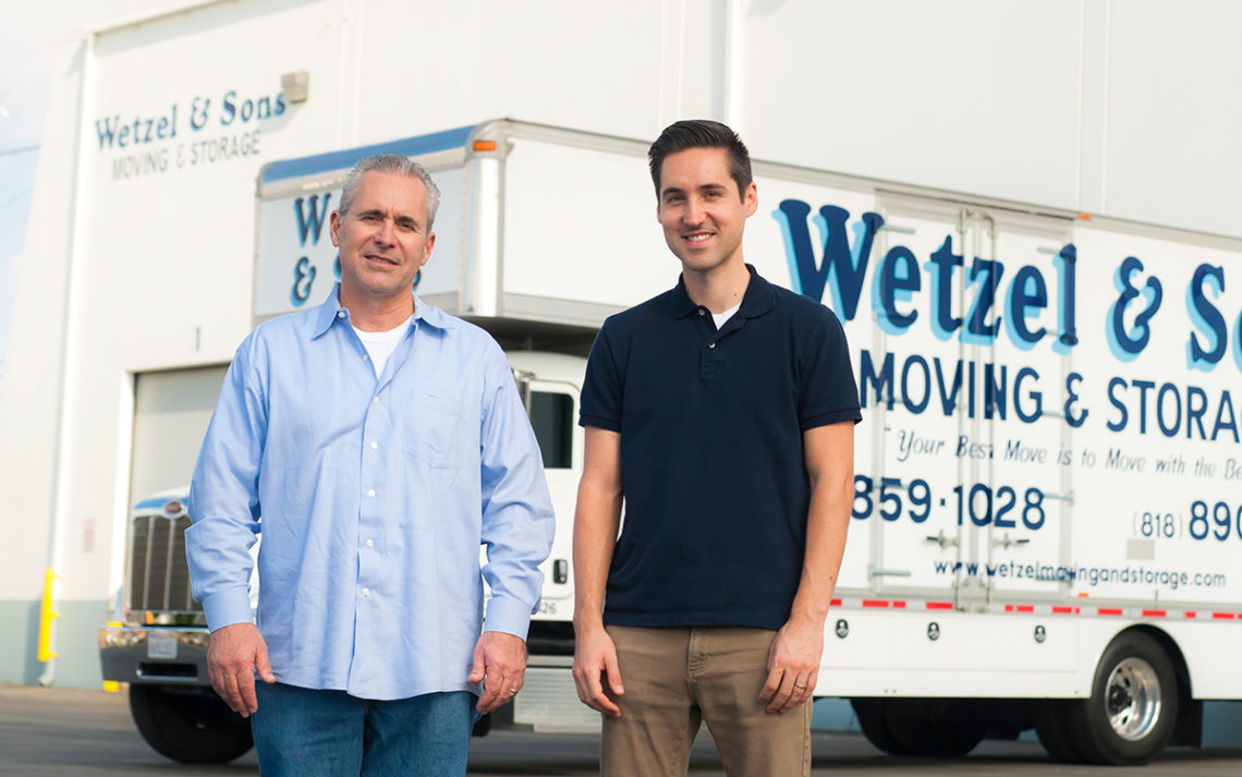The Wetzels stand in front of their storage facility and a truck