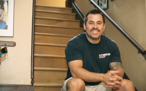 Erich Muller, owner of All City Hardwood Floors, sits on hardwood stairs he refinished.