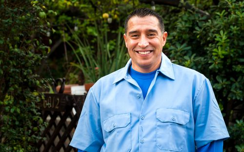 Danny Garcia of DG Plumbing smiles in a garden