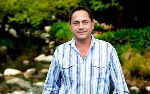 HVAC repairman Emilio Sanchez, owner of ESP Heating & Air, stands by a creek.