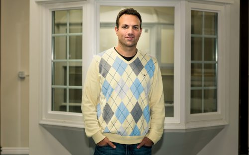 Yoni Barlev of Frontline Windows & More stands in his showroom in front of a window.