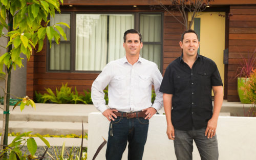 Stephen Gabor and Patrick Allen of Gabor + Allen smile in front of  a remodeled home