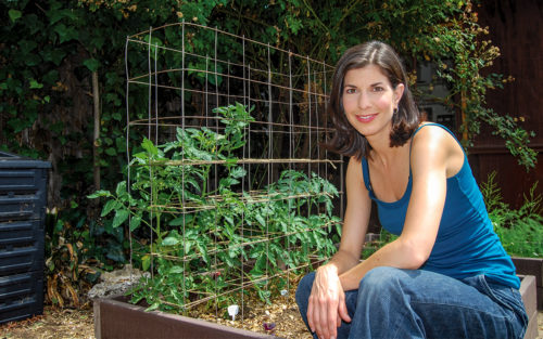 Gardenerd's owner, Christy Wilhelmi, sitting on a vegetable garden's raised bed with a compost bin in the background.