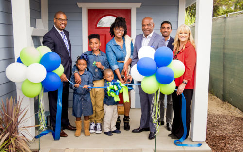 A family cuts the ribbon in a celebration of their new Habitat for Humanity house.