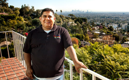 Luis Gonzalez of Hollywood Hills Window Cleaning stands on a job site balcony with the Los Angeles skyline behind him.
