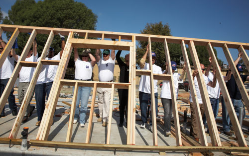 Volunteers for Homes4Families braise a wall together for a home