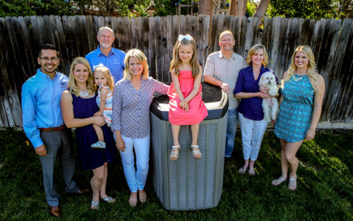 JW Heating and Air owners, Jeff and Michelle Williams, with their family in a backyard with an air conditioning unit