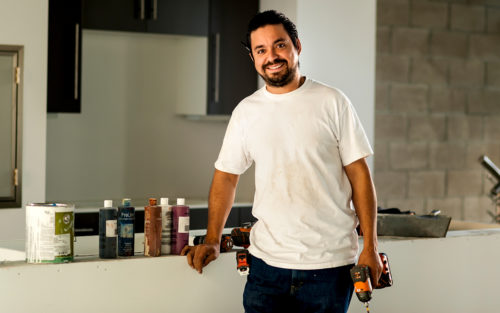Juan Carlos Mancilla smiles at a worksite with painting equipment and paint