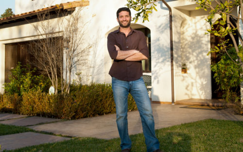 Mickey Granot of Karma Builders, Inc. stands in front of client's home