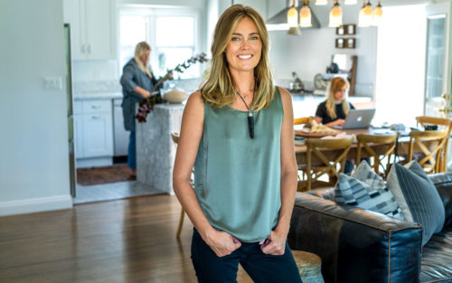Interior designer Lauren Martin-Moro stands in a dining room with blue-white walls and an oak table.