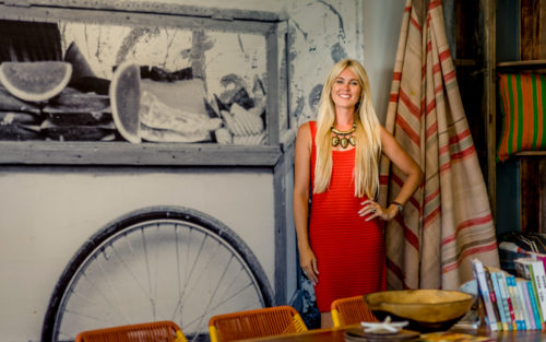 Interior designer Lauren Martin-Moro sits in a dining room with colorful wallpaper and wooden table and chairs.