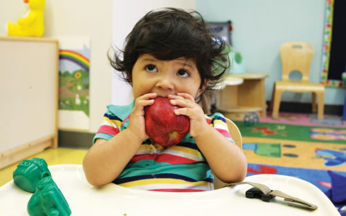 A little girl bites into an apple