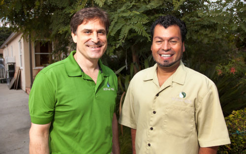 Bryan Angstman and Job Herrera of Naturally Green stand in front of trees