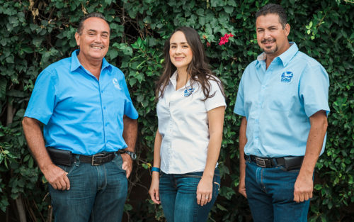 Daniel, Marisol, and Mike of Premier Pool Plastering stand on front of a hedge.