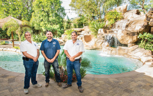Daniel, Marisol, and Mike of Premier Pool Plastering stand on front of a swimming pool.