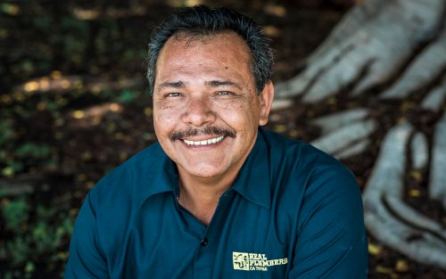 Real Plumbers owner, Jose Cabrales smiles in front of a tree.