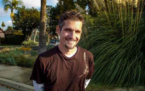 Steve Siegrist in front of a drought tolerant garden he designed and installed.